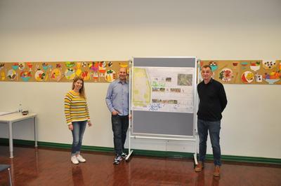 Foto: Eine Frau und zwei Männer stehen neben einer Tafel.